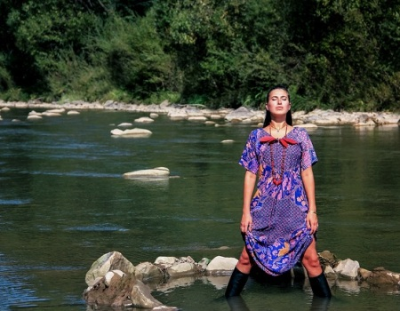A Brunette Girl Stands Knee-deep In A Mountainous Green River In